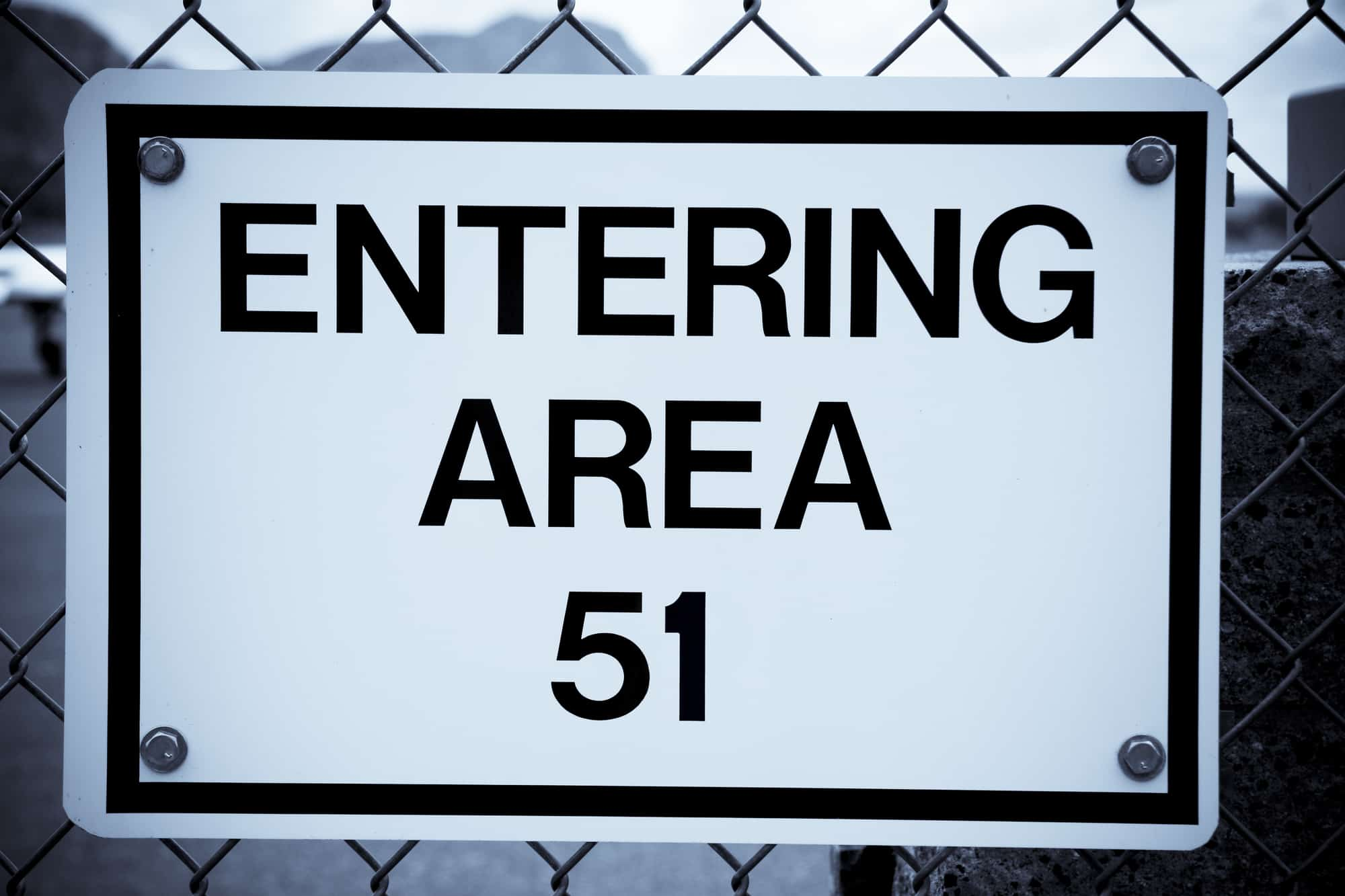 Sign on a chain link fence reading Entering area 51