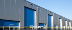 A row of blue garage doors on a commercial facility.