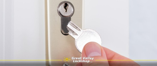 Homeowner holds a broken key in front of a door lock.