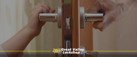 Two people hold opposite handles of a door lock.