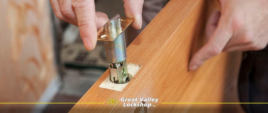 A homeowner installs a door lock in a wooden door.