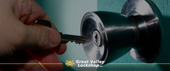 A hand holds a key up to a double cylinder lock.