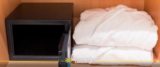 Unlocked hotel safe next to fresh bath robes.