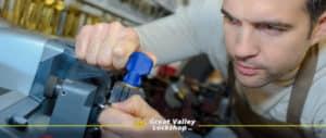 a locksmith uses a machine to cut a key