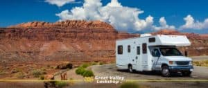 motorhome driving on the street with red rock mountains in the background