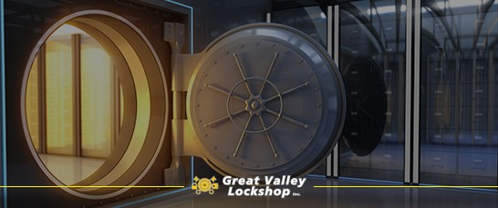 Heavy armored safe door open with gold inside a secure vault.