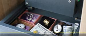 A residential safe is open showing the contents of money and jewlery.